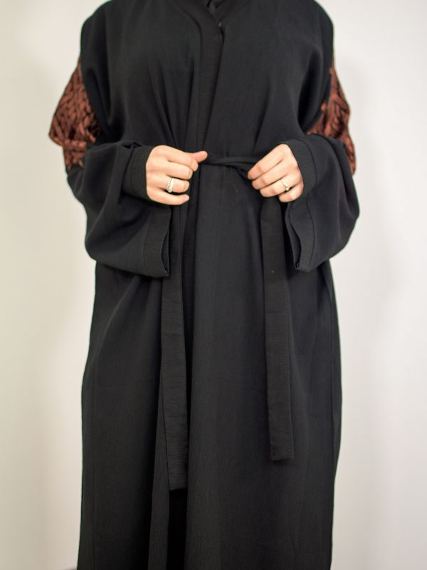 A hijab woman wearing a black modern abaya showing the front belt that is optional to wear with the abaya