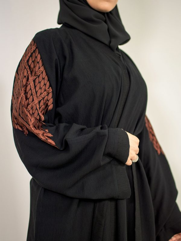A modest woman wearing the black harmony abaya with the beautiful arabic thread embroidery showing on her sleeves